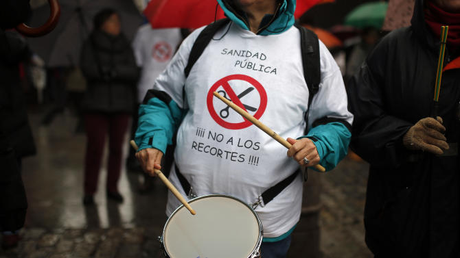 """A protestor plays drum as she wears a t-shirt reading """"public healthcare system"""" and """"No to financial cuts"""" during a demonstration against the government's plans to part privatize the regional healthcare system in Madrid, Spain, Sunday, Jan. 19, 2014. (AP Photo/Andres Kudacki)"""