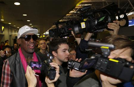 Former NBA basketball player Dennis Rodman talks to journalists as he arrives at the Beijing Capital International Airport to leave for Pyongyang, in Beijing