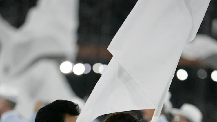 In this Friday Aug. 13, 2004 file photo, South Korean volleyball player Ku Min-jing, right, and North Korean former basketball player Kim Seong Ho carry a unification flag symbolizing one Korea during the Opening Ceremony of the 2004 Olympic Games in Athens. South Korean organizers for this year's Asian Games said Tuesday they've asked the International Olympic Committee to help bring North Korea to the quadrennial sports events