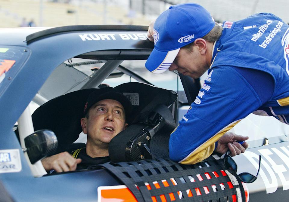 Kurt Busch, left, talks with Brad Keselowski, right, during qualifying for the NASCAR Sprint Cup Series auto race, Friday, Nov. 9, 2012, at Phoenix International Raceway in Avondale, Ariz. (AP Photo/Paul Connors)