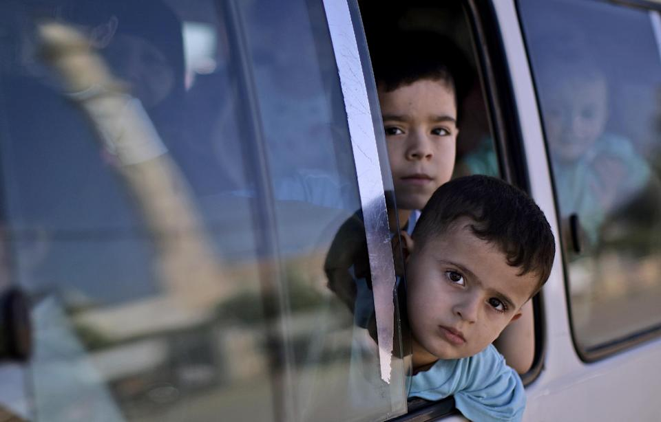 Syrian children, displaced with their family from Aleppo, due to government shelling, look out from a vehicle while crossing Bab Al-Salameh border heading to Turkey, near the Syrian town of Azaz, Sunday, Sept. 9, 2012. (AP Photo/Muhammed Muheisen)