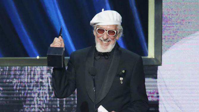 Producer Lou Adler comes to the podium as he is inducted into the Rock and Roll Hall of Fame during the Rock and Roll Hall of Fame Induction Ceremony at the Nokia Theatre on Thursday, April 18, 2013 in Los Angeles. (Photo by Danny Moloshok/Invision/AP)