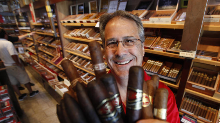 "The owner of Havana Connections cigar shop, George ""Shorty"" Koebel, holds a bunch of cigars at his store in Richmond, Va., Wednesday, June 20, 2012.  The Food and Drug Administration intends to regulate cigars under a 2009 law that gave it authority over the tobacco industry and cigar makers and aficionados are pushing to ensure their livelihoods and the products they enjoy. (AP Photo/Steve Helber)"