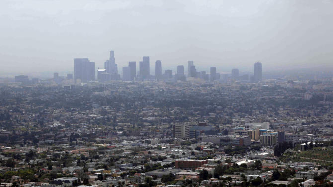 FILE - This April 28, 2009 file photo shows smog covering downtown Los Angeles. In its first major regulation since the election, the Obama administration will impose a new air quality standard that reduces by 20 percent the maximum amount of soot released into the air from smokestacks, diesel trucks and other sources of pollution. The Environmental Protection Agency (EPA) is set to announce the new standard on Friday, meeting a court deadline in a lawsuit by 11 states and public health groups.  (AP Photo/Nick Ut, File)