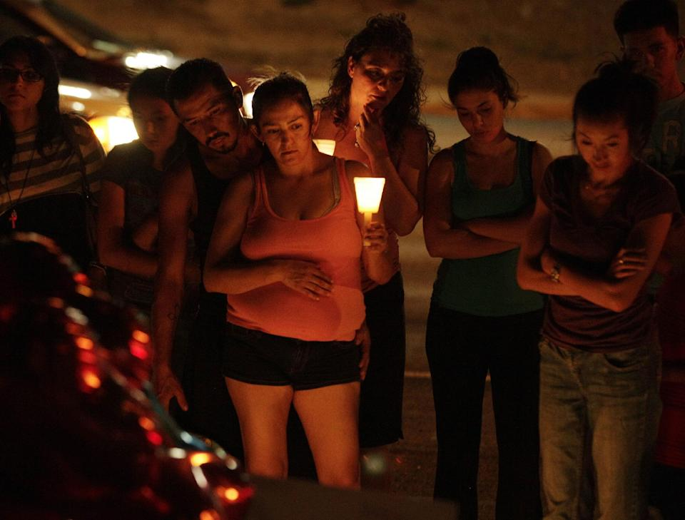 People hold candles as they view a growing memorial, Saturday, July 21, 2012, near the movie theater in Aurora, Colo. where a gunman killed at least 12 people and wounded dozens of others Friday in one of the deadliest mass shootings in recent U.S. history. (AP Photo/Ted S. Warren)