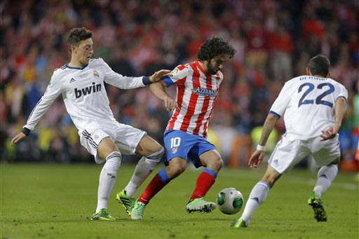 Atletico de Madrid's Arda Turan from Tukey, center, duels for the ball with Real Madrid's Angel Di Maria from Argentina, right, and Mesut Ozil from Germany during their Copa del Rey final soccer match