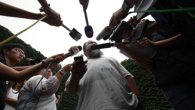 Dissident artist Ai Weiwei, center, speaks to journalists after a verdict was announced in his lawsuit against the Beijing tax authorities in Beijing, China, Friday, July 20, 2012. A Beijing court on Friday rejected an appeal by artist and government critic Ai  against a more than $2 million fine for tax evasion, which he says is part of an intimidation campaign to stop him from criticizing the government. (AP Photo/Ng Han Guan)