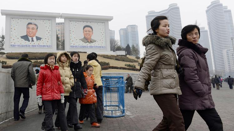 People walk near giant portraits of late North Korean leaders, Kim Il Sung, left, and his son Kim Jong Il, in Pyongyang, North Korea, Tuesday, Jan. 29, 2013. North Korea appears all set to detonate an atomic device, but confirming the explosion when it takes place will be virtually impossible for outsiders, specialists said Tuesday. North Korea watchers in South Korea are speculating diverse dates for a possible nuclear test, with some predicting that could happen as early as this week and others choosing the days just before the Feb. 16 birthday of Kim Jong Il. (AP Photo/Kyodo News)  JAPAN OUT, MANDATORY CREDIT, NO LICENSING IN CHINA, HONG KONG, JAPAN, SOUTH KOREA AND FRANCE