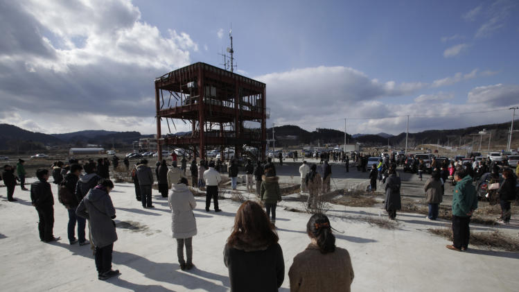 Gathering around what is left of a disaster control center devastated by the March 11, 2011 earthquake and tsunami, people bow their heads Monday, March 11, 2013 in Minamisanriku, Miyagi prefecture, Japan, in a moment of silence at 2:46 p.m. when the magnitude 9.0 earthquake struck off Japan's northeastern coast. Japan marked the second anniversary on Monday of a devastating disasters that left nearly 19,000 people dead or missing. (AP Photo/Shizuo Kambayashi)