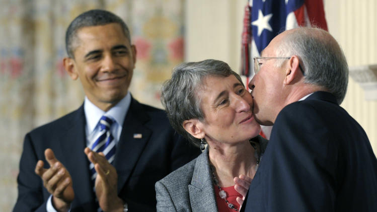 FILE - In this Feb. 6, 2013 file photo, President Barack Obama watches as his Interior Secretary nominee, REI Chief Executive Officer Sally Jewell, center, gets a kiss from outgoing Interior Secretary Ken Salazar in the State Dining Room of the White House in Washington, where the president announced that Jewell is his choice to replace Salazar. (AP Photo/Susan Walsh, File)
