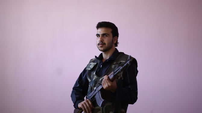 Syrian rebel fighter, Amir Hajji, 20, poses for a picture, after returning back from fighting against Syrian army forces in Aleppo, at a rebel headquarters in Marea on the outskirts of Aleppo city, Syria, Sunday, Aug. 26, 2012. In their previous lives, they were butchers, barbers, construction workers and university students. Now they are rebels fighting a civil war they hope will end the regime of Syrian President Bashar Assad.  (AP Photo/Muhammed Muheisen)