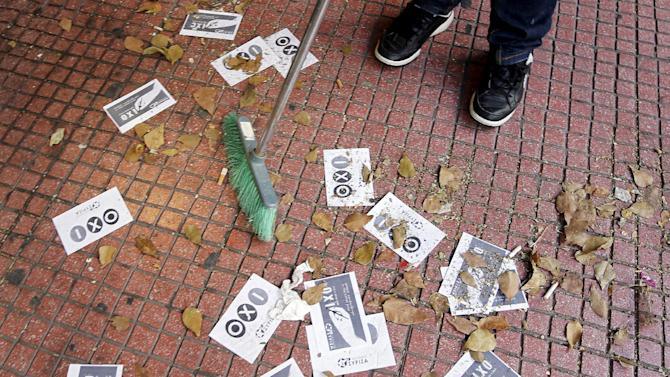 "A shop owner cleans the pavement with referendum campaign leaflets reading ""No"" in Greek in Athens"