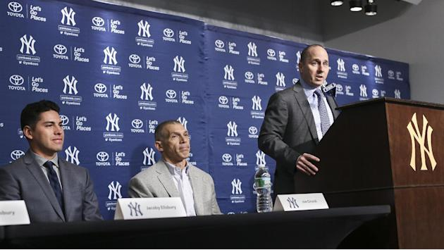Brian Cashman, general manager of the New York Yankees, speaks during a news conference alongside team manager Joe Girardi, center, and Jacoby Ellsbury, left, at Yankee Stadium, Friday, Dec. 13, 2013,