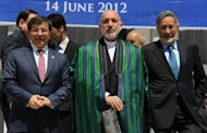 Afghan President Hamid Karzai (C) poses with Turkish Foreign Minister Ahmet Davutoglu (L) and his Afghan counterpart Zalmai Rasool (R) at the conclusion of the Heart of Asia Ministerial Conference at the Foreign Affairs Ministry in Kabul
