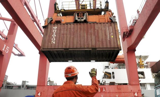 An employee guides as a crane unloads shipping containers from a cargo ship at a port in Lianyungang