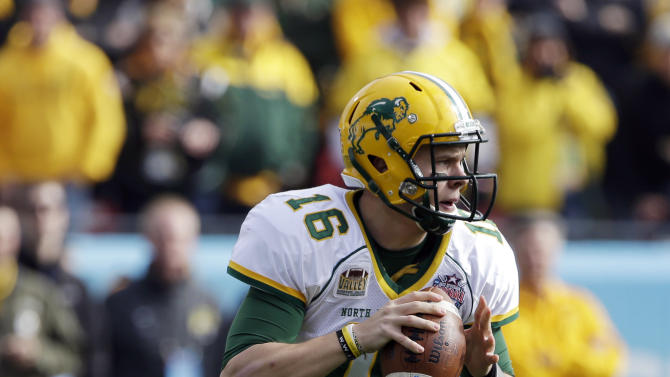 North Dakota State quarterback Brock Jensen rolls out of the pocket as he prepares to throw a pass during the first half of the FCS Championship NCAA college football game against Sam Houston State, Saturday, Jan. 5, 2013, in Frisco, Texas. (AP Photo/Tony Gutierrez)