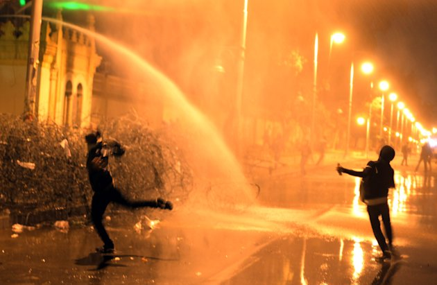 Egyptian protesters throw stones while security police open water cannons on them from inside the grounds of the presidential palace during a demonstration in Cairo, Egypt, Monday, Feb. 11, 2013. Secu