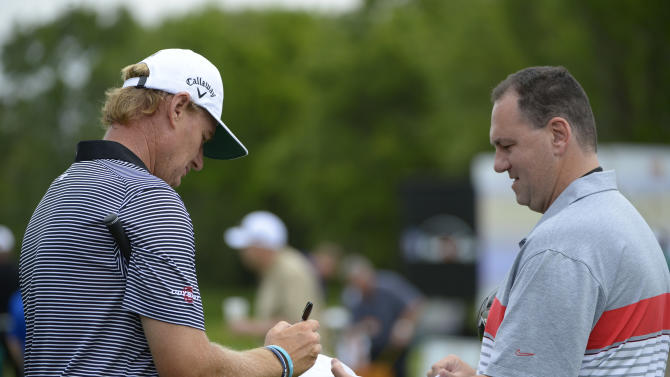 Ernie Els, left, of South Africa, signs an autograph while walking off the driving range during the pro-am of the Arnold Palmer Invitational golf tournament in Orlando, Fla., Wednesday, March 20, 2013.(AP Photo/Phelan M. Ebenhack)