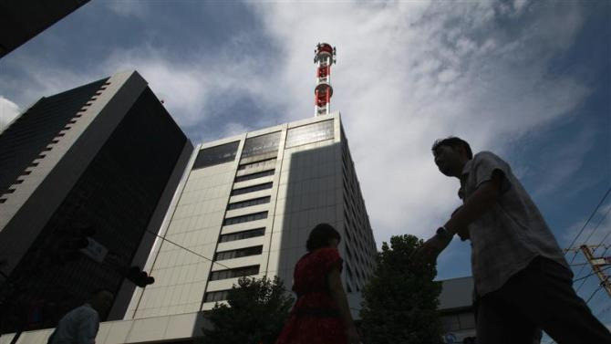 Pedestrian walks past Tokyo Electric Power Co headquarters in Tokyo