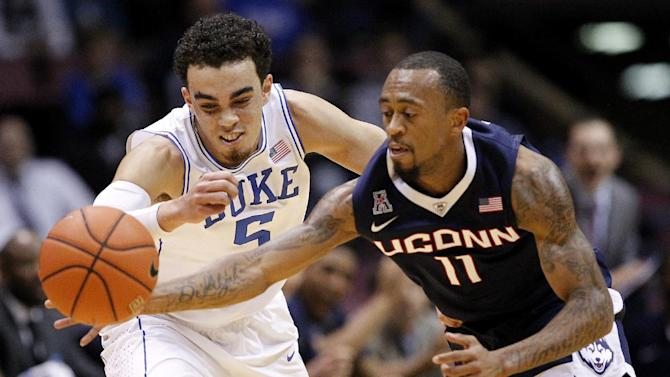Connecticut guard Ryan Boatright (11) makes a steal against Duke guard Tyus Jones (5) during the first half of an NCAA college basketball game, Thursday, Dec. 18, 2014, in East Rutherford, N.J. (AP Photo/Julio Cortez)