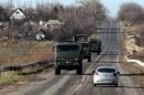 Military trucks are seen through a car window as they drive along a road on the territory controlled by the self-proclaimed Donetsk People's Republic in Bezimenne, eastern Ukraine
