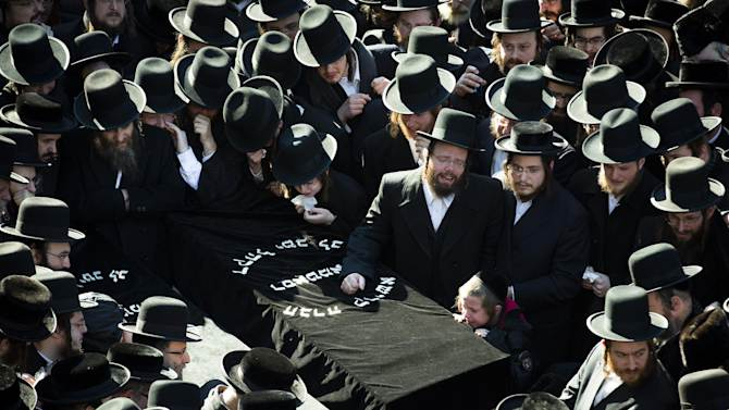 Members of the Satmar Orthodox Jewish community congregate for the funeral of two expectant parents who were killed in a car accident, Sunday, March 3, 2013, in the Brooklyn borough of New York. A driver struck the car the couple were riding in early Sunday morning, killing both parents while their baby, who was born prematurely, survived and is in critical condition. (AP Photo/John Minchillo)