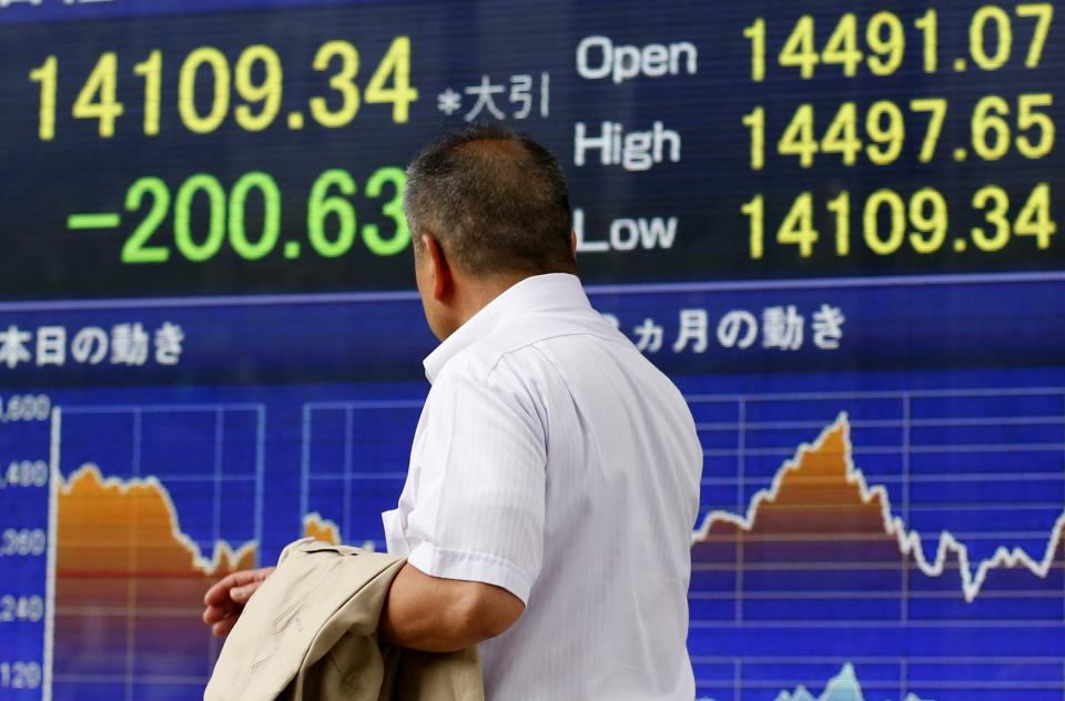 A man watches an electronic stock indicator in Tokyo, Monday, July 8, 2013. Concern over China's slowdown weighed on Asian stock markets Monday after the head of the International Monetary Fund warned of a loss of momentum in emerging economies. (AP Photo/Shizuo Kambayashi)