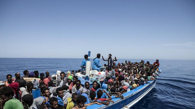 Migrants on a packed wooden boat wait to be rescued off the coast of Malta