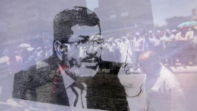 Hundreds of Muslim Brotherhood supporters are seen through a transparent poster of President Mohammed Morsi during a demonstration outside the State Council in Cairo, Egypt, Tuesday, July 17, 2012, ahead of an anticipated Administrative Court ruling on the panel writing the new constitution. Hundreds of Islamist protesters encircled a court building in Egypt, while others squabbled with lawyers in a highly tense court session where judges were to issue a key verdict regarding legality of a panel tasked to write the new constitution.(AP Photo/Amr Nabil)