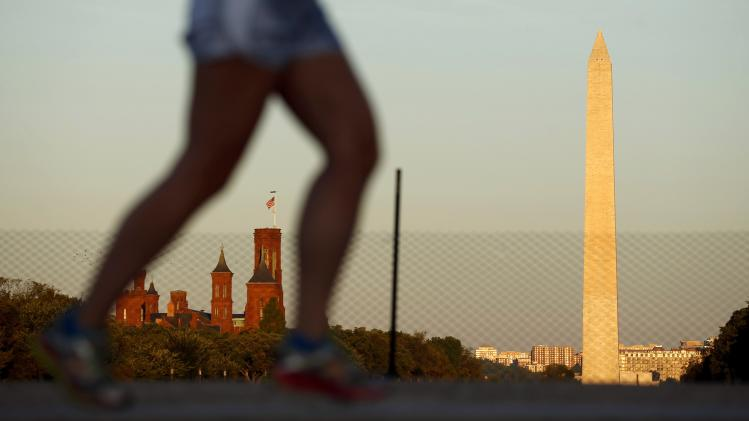 The Smithsonian Castle and the Washington Monument are seen as a woman jogs along the National Mall in Washington