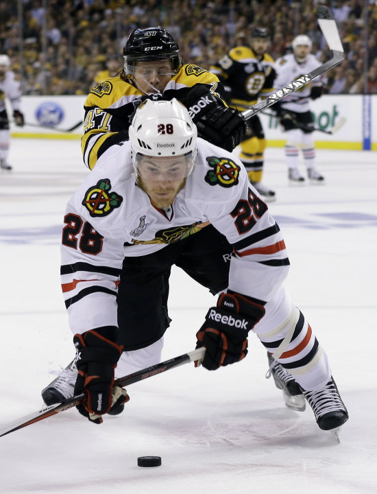 Boston Bruins defenseman Torey Krug (47) checks Chicago Blackhawks right wing Ben Smith (28) to the ice during the first period in Game 3 of the NHL hockey Stanley Cup Finals in Boston, Monday, June 1