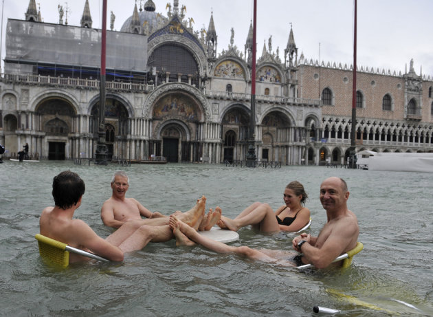 People sit at the table of a bar in a flooded St. Mark's Square in Venice, Italy, Sunday, Nov. 11, 2012. High tides have flooded Venice, leading Venetians and tourists to don high boots and use wooden walkways to cross St. Mark's Square and other areas under water. Flooding is common this time of year and Sunday's level that reached a peak of 58.66 inches (149 centimeters) was below the 63 inches (160 centimeters) recorded four years ago in the worst flooding in decades. (AP Photo/Luigi Costantini)