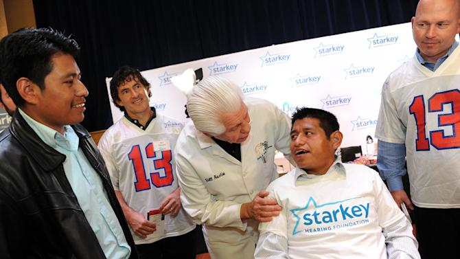 Bill Austin, founder of Starkey Hearing Foundation, listens to migrant worker 31-year-old Bersaien Lopez hear and voice his first sounds after he fits him with a new hearing aid, as his brother Jose Lopez watches, on Saturday, Feb. 2, 2013 in New Orleans. (Photo by Cheryl Gerber/Invision for Starkey Hearing Foundation/AP Images)