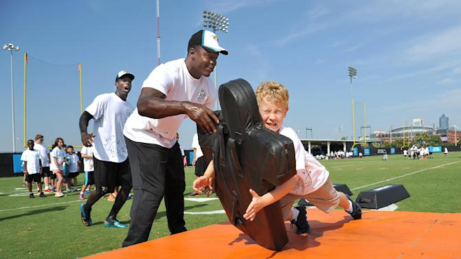 Jacksonville Jaguars' Marcus Whitfield holds the blocking dummy as Hunter Speight, right, 10, hits it during a linebacker drill at an NFL football Jacksonville Jaguars' Got Skills Rookie Day on Friday, June 20, 2014, in Jacksonville, Fla