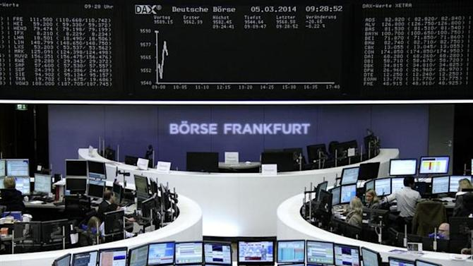 Traders are pictured at their desks in front of the DAX board at the Frankfurt stock exchange March 5, 2014. REUTERS/Remote/Stringer
