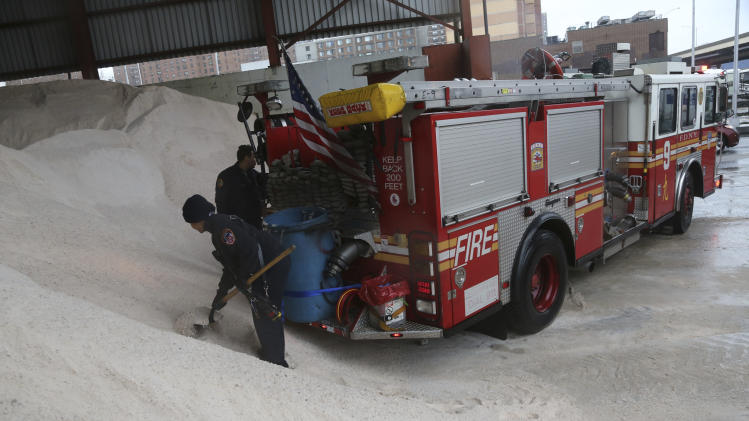 Firefighters load salt onto a container in the back of their truck at a Sanitation Department depot, Friday, Feb. 8, 2013 in New York. A storm poised to dump up to 3-feet of snow from New York City to Boston and beyond beginning Friday could be one for the record books, forecasters warned, as residents scurried to stock up on food and water and road crews readied salt and sand.  (AP Photo/Mary Altaffer)