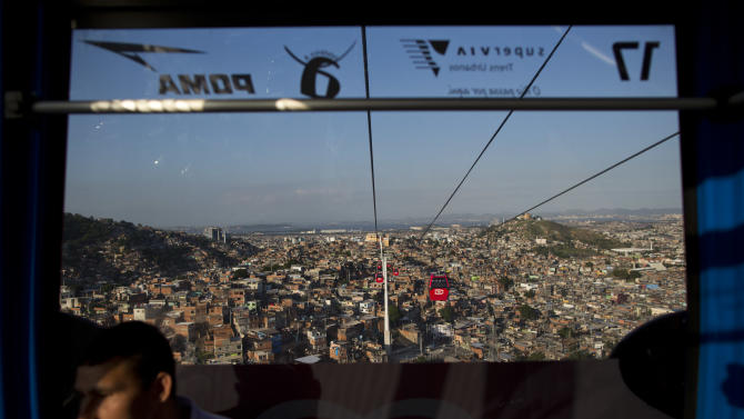 In this May 10, 2013 photo, a resident commutes inside a cable-car over the Complexo do Alemao complex of shantytowns in Rio de Janeiro, Brazil.  The cable-car system linking six of its hilltops over a 3.5-kilometer (2.3-mile) route has become a popular tourist attraction. (AP Photo/Felipe Dana)
