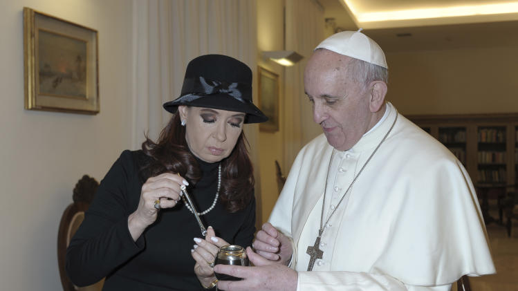 FILE - In this March 18, 2013 file photo provided by the Vatican paper L'Osservatore Romano, Pope Francis is presented a mate gourd and straw, to hold the traditional Argentine tea, by Argentine President Cristina Fernandez, during their meeting at the Vatican. Catholic doctrine considers the pope to be God's delegate on Earth. That alone might explain the remarkable about-face that Argentina's president and most of her followers have managed to pull off in the days since the cardinal she treated as a political arch-enemy became Pope Francis. (AP Photo/L'Osservatore Romano, File)