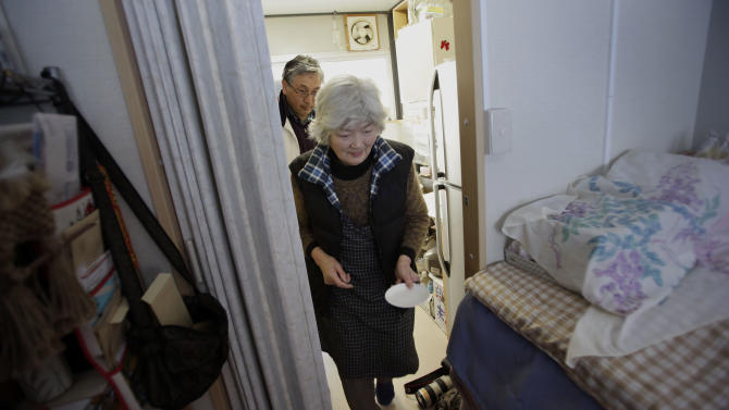 In this Saturday, Feb. 23, 2013 photo, Hide Sato, 83,  brings a plate to her room as her nephew and city council member Kazuyoshi Sasaki follows,  at a temporary housing complex in Rikuzentakata, Iwate Prefecture, northeastern Japan. Like tens of thousands of people who lost everything in the tsunami that pulverized Japan's northeastern coast two years ago,  Sato is living in one-room temporary housing, and longing for a home of her own. (AP Photo/Junji Kurokawa)