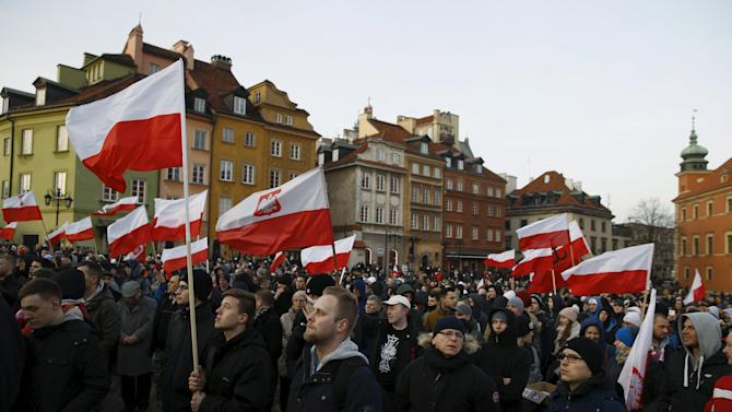 Protesters hold flags as they gathers during anti-immigrant rally in front of the Royal Castle in Warsaw