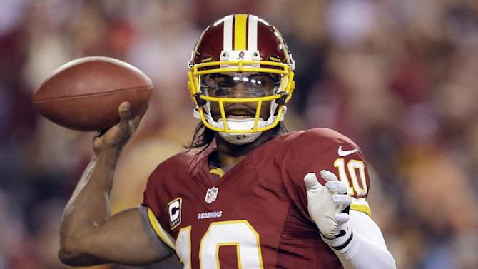 FILE - In this Jan. 6, 2013, file photo, Washington Redskins quarterback Robert Griffin III passes the ball during the second half of an NFL wild card playoff football game against the Seattle Seahawks in Landover, Md. Griffin has won The Associated Press 2012 NFL Offensive Rookie of the Year award, beating out two other sensational first-year quarterbacks, it was announced on Saturday, Feb. 2, 1013. (AP Photo/Matt Slocum, File)