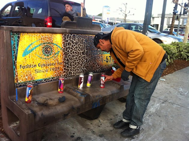 Phil Furtado places candles on a burned city bus bench in Los Angeles on Thursday, Dec. 27,2012. Police arrested a man for allegedly setting a 67-year-old woman on fire who was sleeping on the bus stop bench. A witness said he saw a man come out of the store and pour something on the woman who had been sleeping on a bench before striking a match and setting her ablaze. The woman, who may be homeless, was taken to a hospital and listed in critical condition. (AP Photo/Greg Risling)