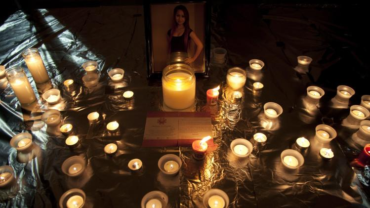 "FILE - In this Friday, Oct. 19, 2012, file photo, candles are displayed in front of a picture of Amanda Todd during a memorial for her in Surrey, British Columbia. In Google's 12th annual roundup of global trending searches, ""Amanda Todd"" was ranked eighth. (AP Photo/The Canadian Press, Jonathan Hayward)"