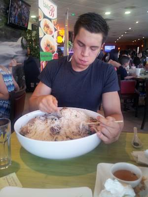 """In this undated photo provided by Eric Dahl, Dahl, a University of Wisconsin computer engineering student with a nickname of """"Silo,"""" fills up on a 13-pound bowl of Vietnamese noodles known as pho. The competitive eater has become a top-ranked competitor nationally, using prize earnings to help pay for his UW-Madison degree. (AP Photo/Aramis Phillip Alvarez)"""