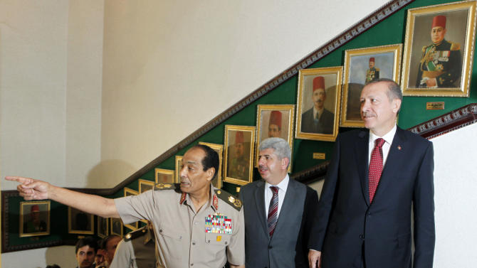 Field Marshal Mohamed Hussein Tantawi, head of Egypt's ruling military council, left, shows to Turkish Prime Minister Recep Tayyip Erdogan, right, paintings of Egyptian defence ministers of the early last century upon his arrival at the defence ministry in Cairo, Egypt, Tuesday, Sept. 13, 2011. Erdogan, intent on broadening Turkey's influence in the Middle East and the Arab world, started a visit to Egypt and will also visit Tunisia and Libya, two other countries where popular uprisings have ousted autocratic leaders. (AP Photo/Amr Nabil, Pool)