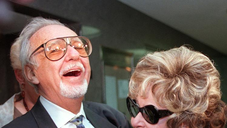 File --  In an April 25, 1997, file photo Burt Pugach laughs with his wife, Linda, in the hallway of the Queens Criminal Court in New York, where Pugach was on trial for threatening another, younger woman, after she left him. Linda Pugach, who was blinded in 1959 when her future husband hired  men to throw lye in her face, died Tuesday, Jan. 22, 2013 in New York. She was 75.  (AP Photo/Emile Wamsteker, file)