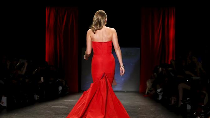 Alexa PenaVega presents a creation during the AHA's Go Red For Women Red Dress Collection at New York Fashion Week