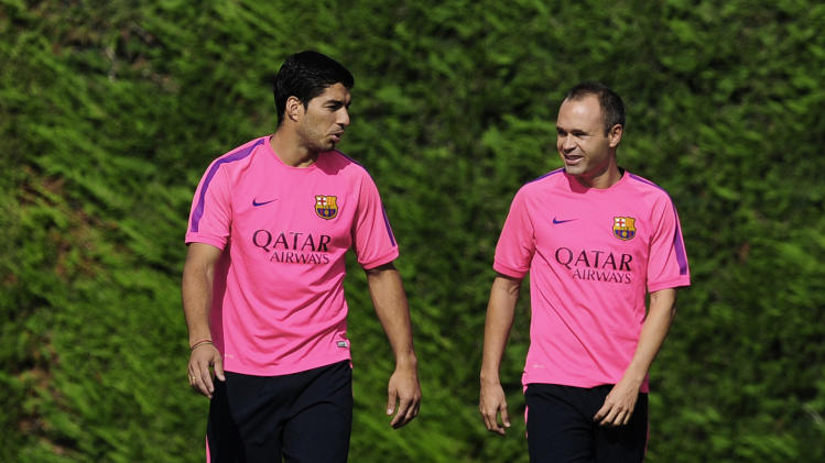 FC Barcelona's Andres Iniesta, right, and Luis Suarez, from Uruguay, talk during a training session at the Sports Center FC Barcelona Joan Gamper in San Joan Despi, Spain, Saturday, Aug. 23, 2014. (AP Photo/Manu Fernandez)