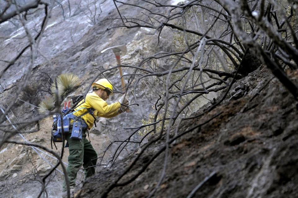 Firefighter Romero Mercado checks for hotspots in the Angeles National Forest Wednesday Sept. 5, 2012 near Los Angeles. Fire crews are getting help from rain in battling a 3,800-acre fire in the San Gabriel Mountains northeast of Los Angeles. (AP Photo/Nick Ut)