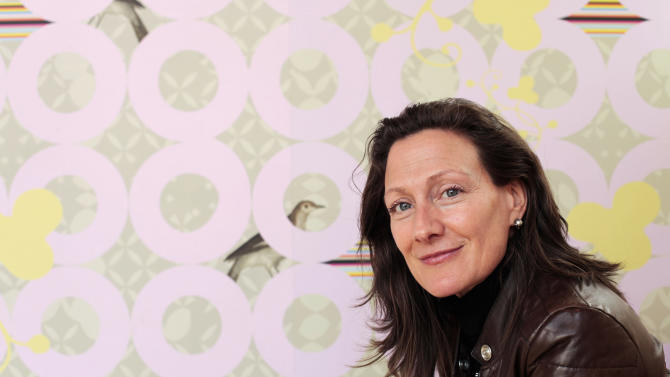 This photo taken Sunday, March 3, 2013, provided by Sarah Rowland shows Sarah Rowland with the wallpaper she designed for Dixie Donuts in Richmond, Va. Owners Betsy Thomas and J Frank asked Rowland to design a custom wallpaper for an accent wall at the shop located in the trendy Carytown section of Richmond. (AP Photo/Sarah Rowland, Jay Paul)